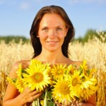 Smiling woman outside holding sunflowers