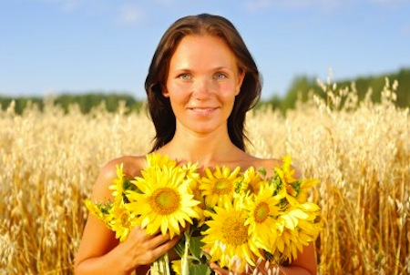 Smiling woman holding sunflowers outside