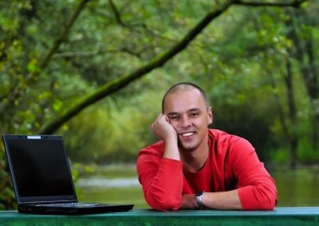 Man with laptop smiling