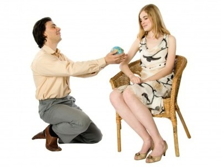 Corny-looking man on one knee proposing to woman