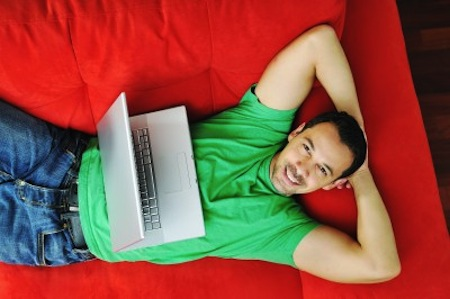 Man lying on couch with laptop