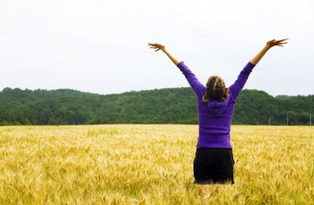 Woman standing in field with victory arms