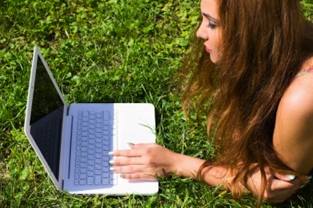 Woman lying on grass with laptop