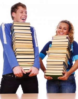 Man and woman holding stacks of books