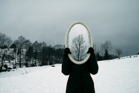Woman holding mirror in front of her face