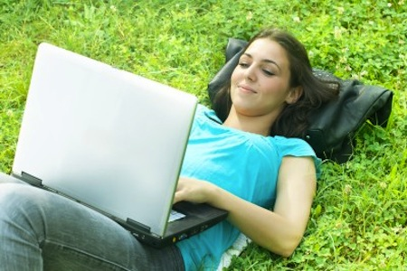 Smiling woman outside lying on grass with laptop